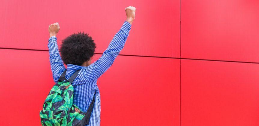 Exemplos de redações nota 1000: fotografia de um homem de costas com as mãos para cima, como se estivesse comemorando algo.