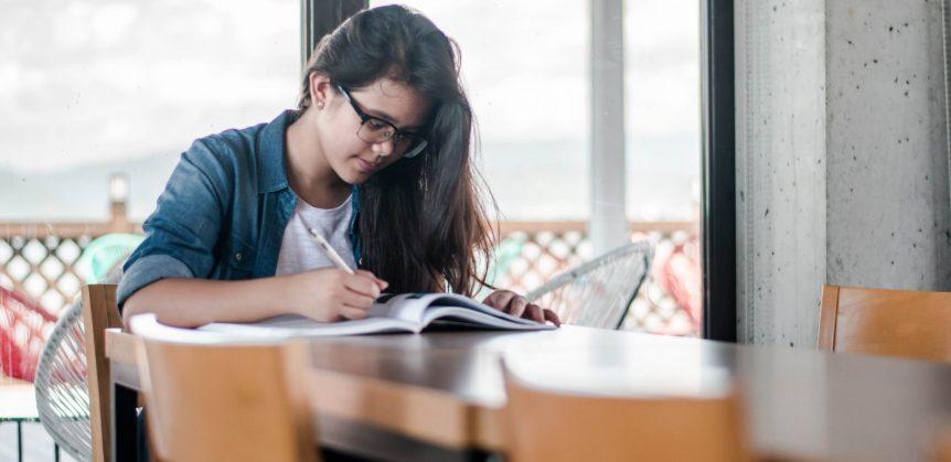 Proposta de intervenção Enem: fotografia de uma mulher sentada à mesa e escrevendo em um livro.